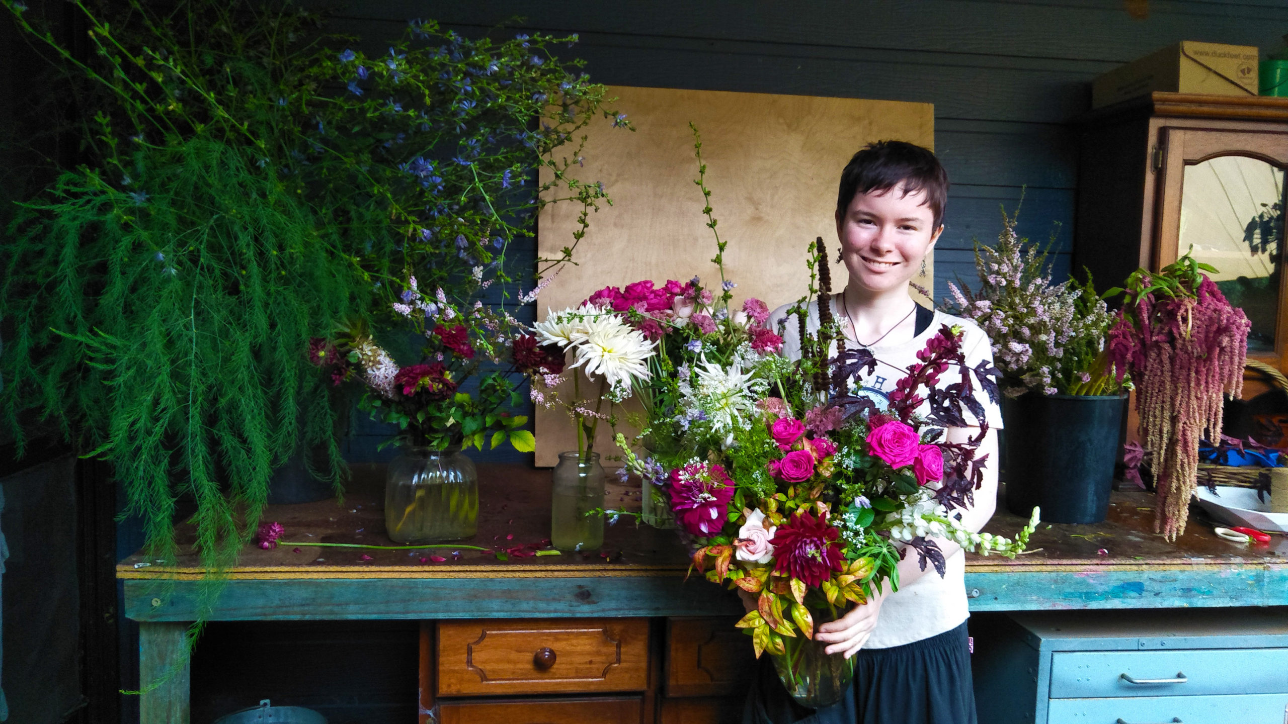 Young women holds a large bunch of flowers in vase. Behind her is a wooden table and drawers with a variety of vases and flowers.