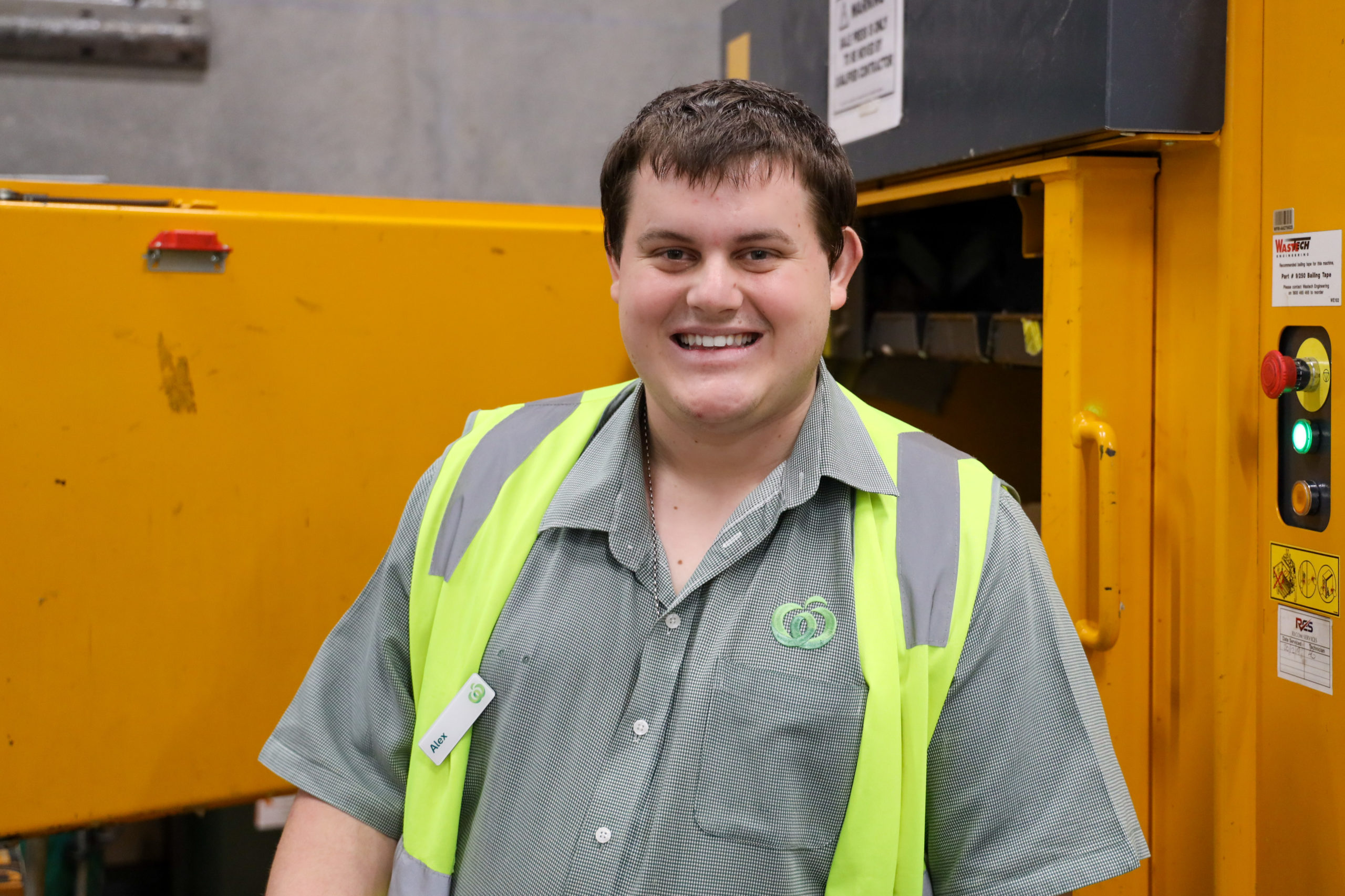 Young man with big smile stand in front of rubbish compacter at Woolworths