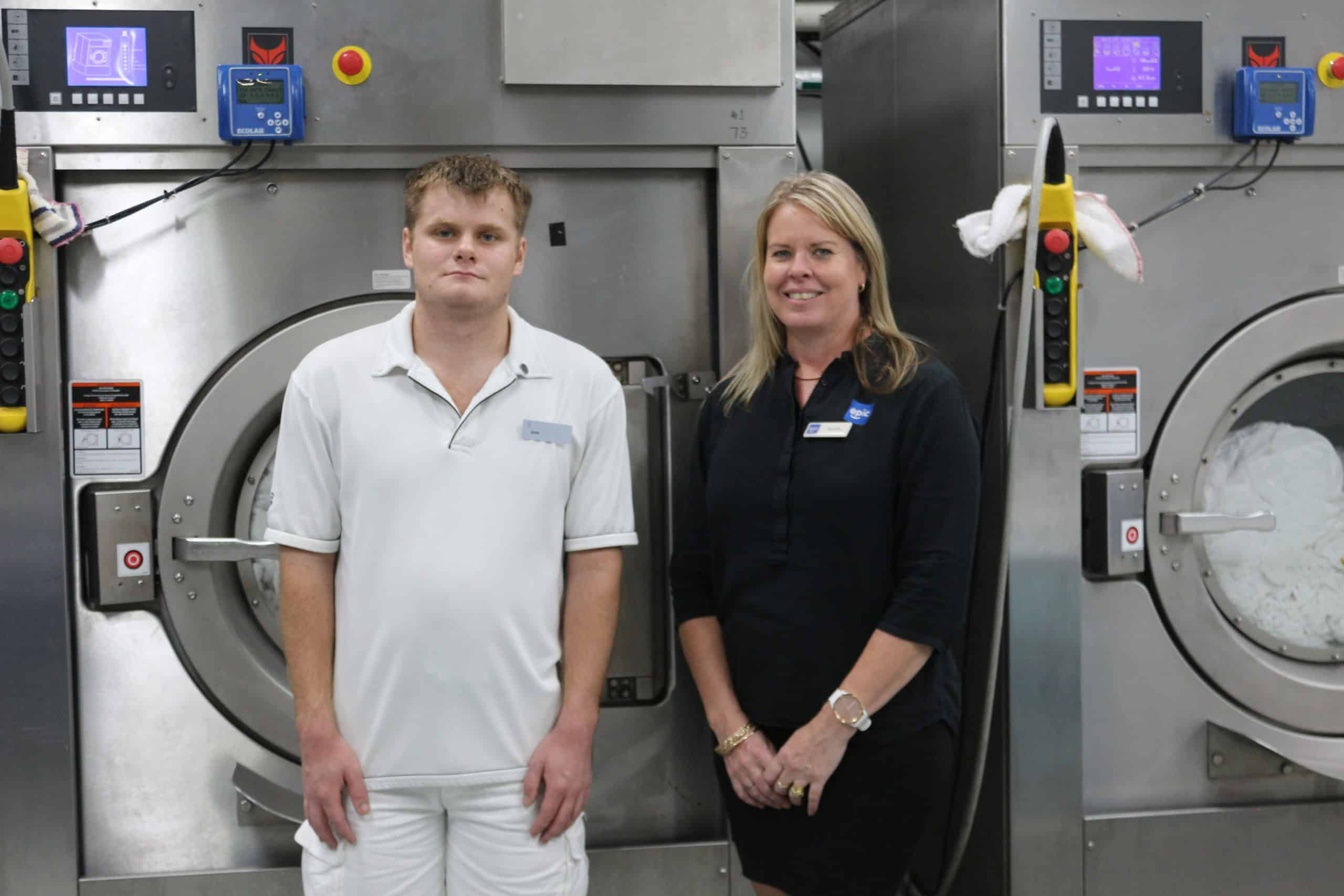 Young man in white polo shirt and shorts stands next to female EPIC staff member in black shirt and skirt, in front of large washing machine