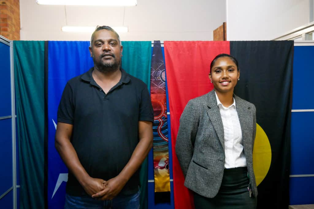 Two indigenous people stand proudly in front of the Aboriginal and Torres Strait Island flags. The man on the left wearing a black polo shirt. The young lady on the right is dressed in smart business attire. They are smiling and show pride in their stance.