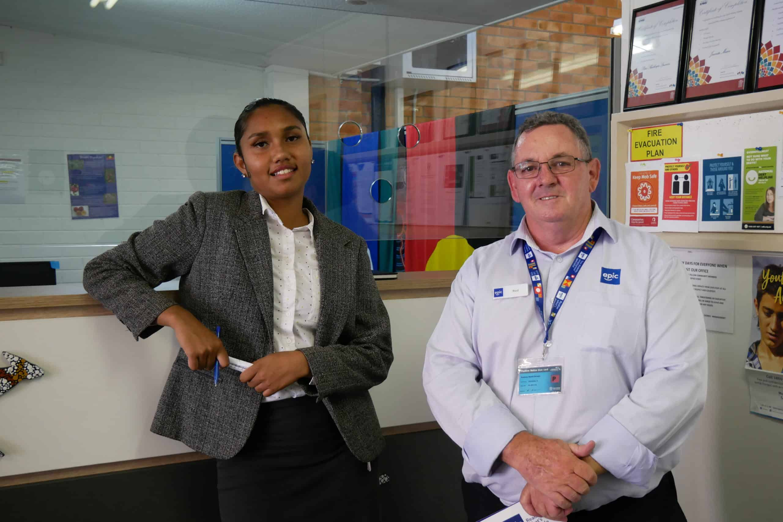Sharnece, an indigenous young women dressed in business attire, stands next to Rod from EPIC Assist in the reception area of Kahwun-Wooga Aboriginal Coorporation in Maryborough