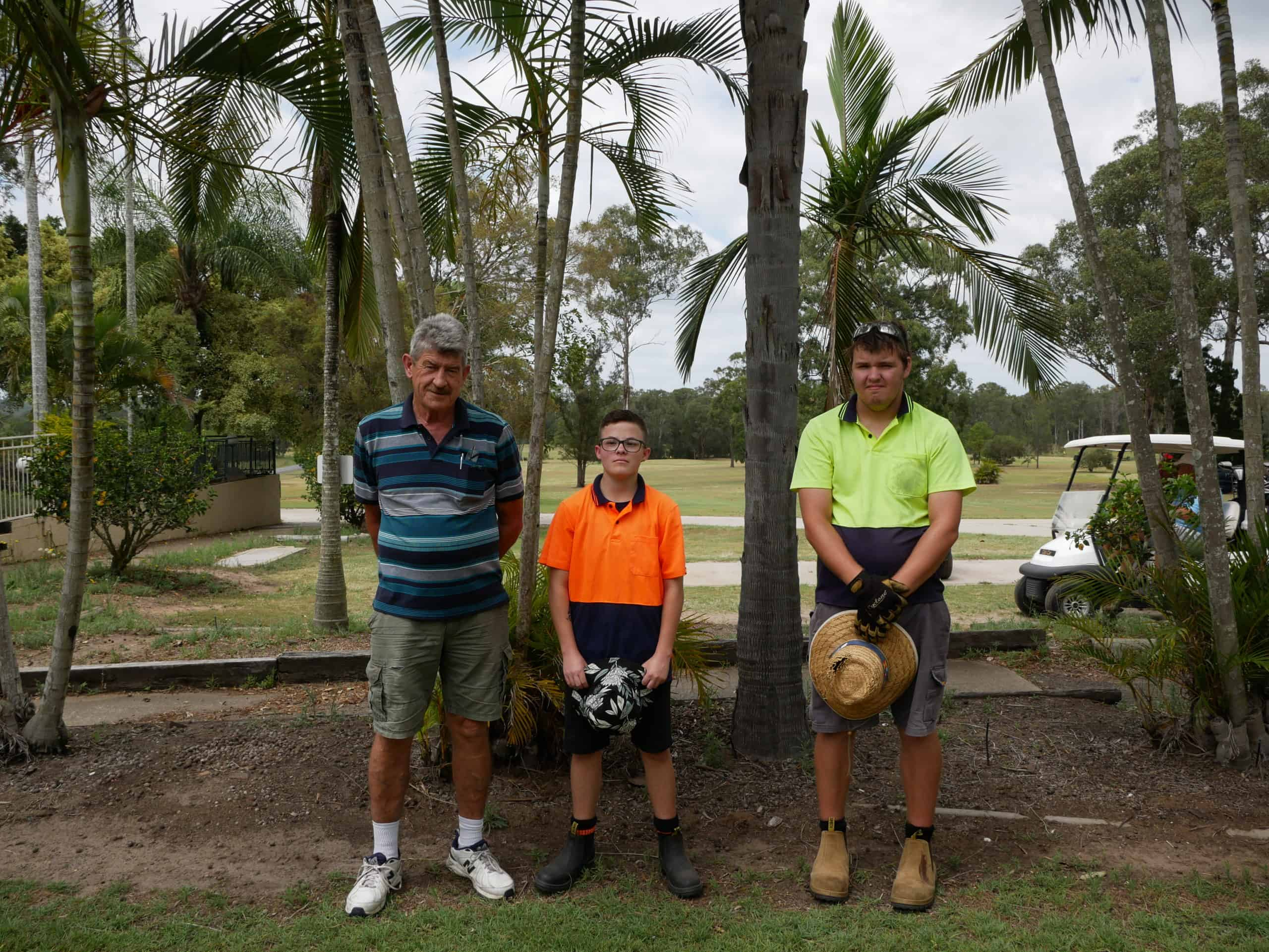 Three men stand in front of palm trees with golf course in the background. One of the men is older and dressed in a polo short and shorts, the other two men are groundskeepers, wearing hi-vis shirts, holding their hats in their hands.