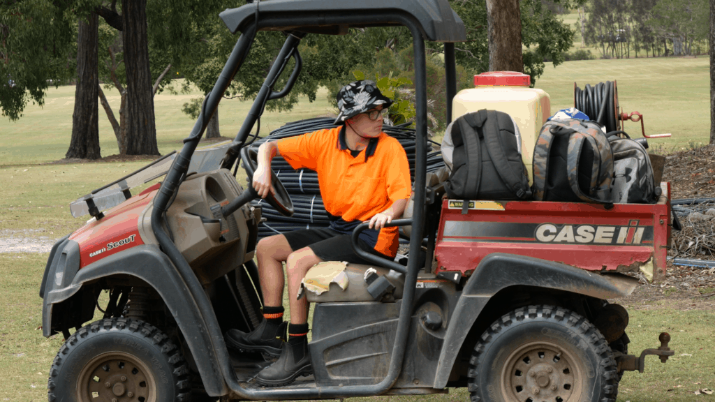 A young man drives a tractor whilst doing maintenance on golf course
